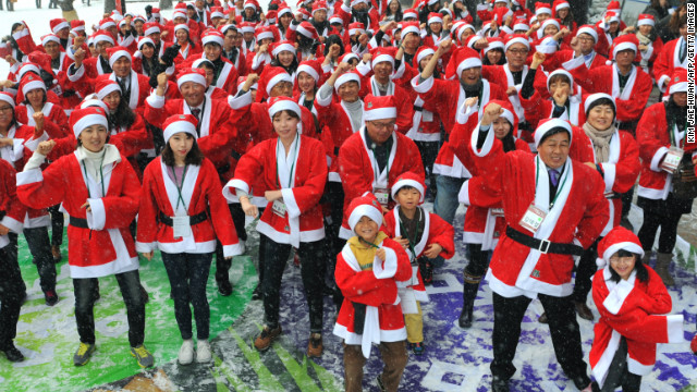 People in Santa Claus outfits imitate South Korean rapper Psy's famous &quot;Gangnam Style&quot; dance outside offices in Seoul, South Korea, on Wednesday, December 5. The dance marked the start of a charity mission to hand out gifts to children.