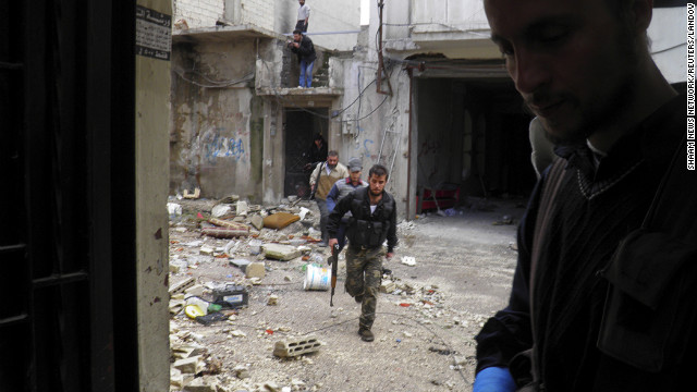 In this handout from the Shaam News Network, Free Syrian Army fighters take cover in destroyed buildings during clashes with forces loyal to Syrian President Bashar al-Assad on December 4.