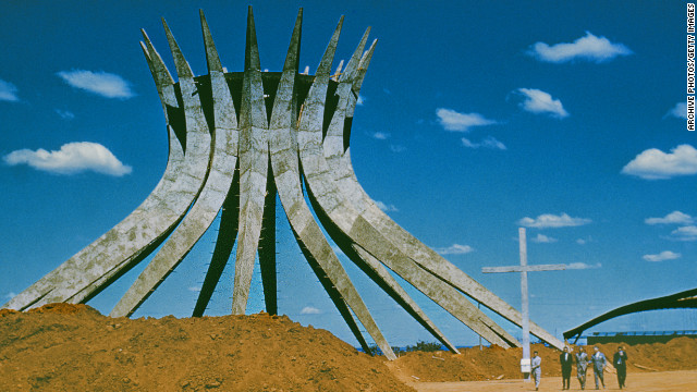 The cornerstone of Niemeyer's <a href='http://catedral.org.br/historia' target='_blank'>Cathedral of Brasilia</a> was laid in 1958. This hyperboloid structure consists of 16 concrete pillars, each weighing 90 tons, and covers a circular area that is 70 feet in diameter. This photo was taken in the 1960s, but the building was finally inaugurated in 1970.