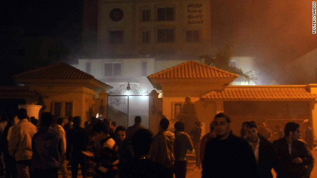 Protesters angry over Egyptian President Mohamed Morsy's decisions giving himself unchecked powers surround the Muslim Brotherhood's headquarters in Cairo after starting a fire inside the compound on Thursday, December 6.