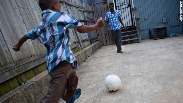 A Bangladeshi boy plays soccer with his father in Baltimore. The child was attacked and mutilated in Dhaka, Bangladesh, in 2010 and was later brought to the U.S., where doctors at Johns Hopkins Children's Center agreed to operate on him for free.