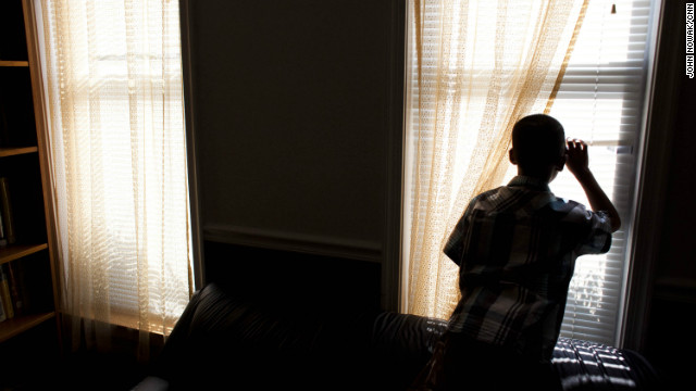 "The boy we refer to as ""Okkhoy"" looks out the window at his temporary home in Baltimore. For his safety, CNN has chosen to withhold his name."
