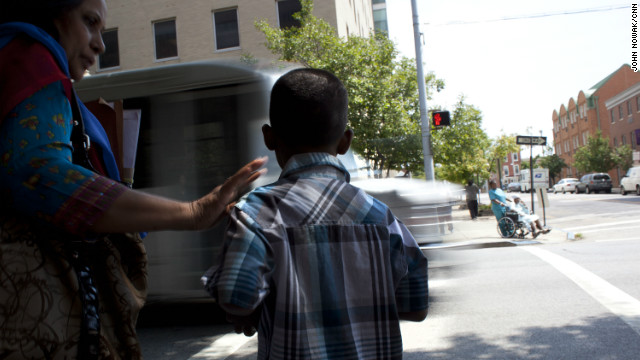 The boy is shown how to cross the busy streets of Baltimore.