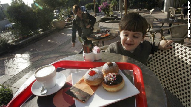 A young Israeli boy looks at a serving of fresh oil-fried and jam-filled doughnuts, known in Hebrew as &quot;sufganiyot&quot;, served at one of the local bakeries in Kadima, central Israel, during Hanukkah.