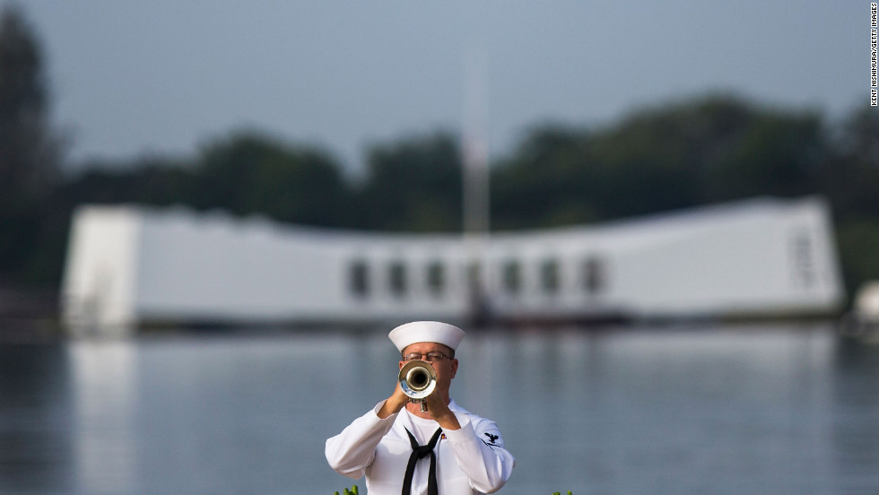 "A U.S. Navy musician plays ""Taps"" in front of the USS Arizona Memorial during the 71st Annual Memorial Ceremony commemorating the WWII attack on Pearl Harbor at the World War II Valor in the Pacific National Monument on Friday, December 7, in Pearl Harbor, Hawaii."