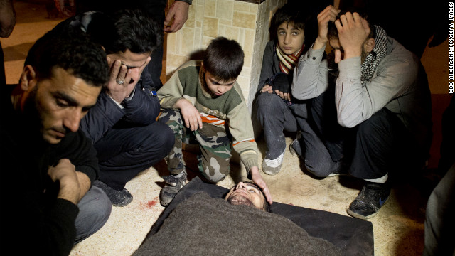 Syrians mourn a fallen rebel fighter at a rebel base in the al-Fardos area of Aleppo on December 8.