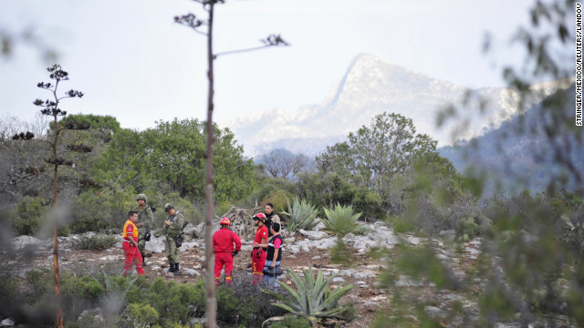 Soldiers and civil protection personnel inspect the perimeter of the crash site. The plane took off from Monterrey, Mexico, and lost contact with air traffic controllers.