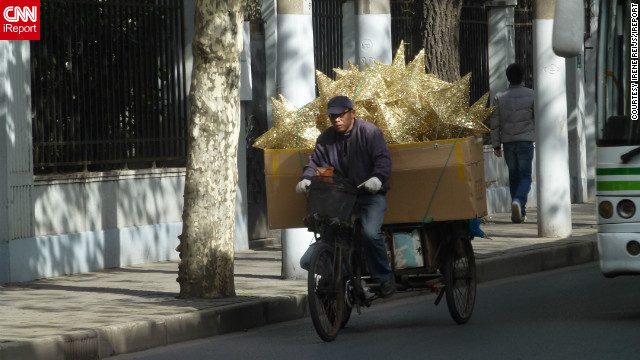"Dutch iReporter <a href=' http://ireport.cnn.com/people/Irenere'>Irene Reijs</a>, captured this image of a man delivering Christmas decorations by bike in her adopted home of Shanghai, China. ""Christmas is not a Chinese tradition, but much of our decorations are made in China,"" she said."
