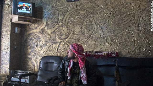 A rebel soldier watches Al-Jazeera news in a shop near the front lines in Aleppo on December 9.