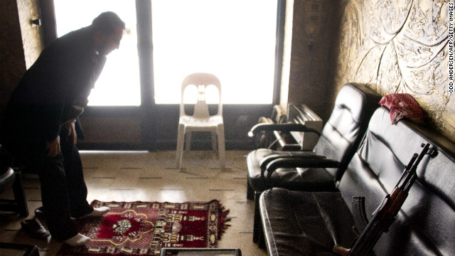 A rebel soldier prays in a shop in Aleppo on December 9.