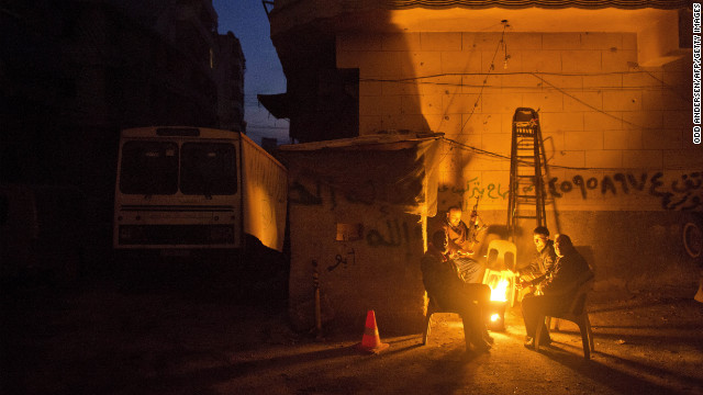 Men warm themselves by a fire on a street corner in Aleppo, Syria, on Sunday, December 9. Click through to view images of the fighting from December, or see photos of the conflict from November.