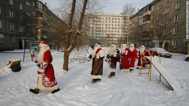 Costumed participants of the annual &quot;Best Father Frost&quot; contest from different city districts make their way through a courtyard in Krasnoyarsk, Russia, on Monday, December 10.
