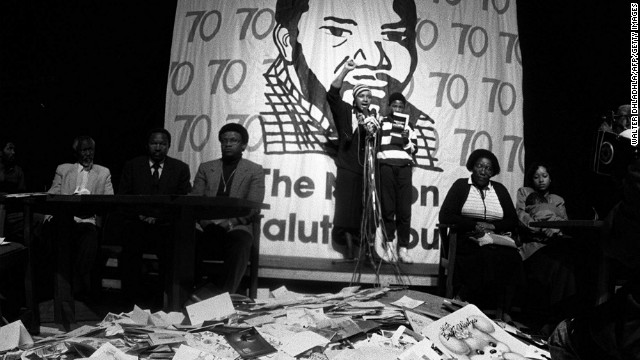 Winnie Mandela addresses a crowd of supporters in Johannesburg in 1988, standing in front of a pile of cards addressed to her husband at an event marking his 70th birthday. She led an international campaign calling for his release.