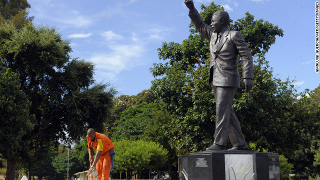 An inmate at the Groot Drakenstein Prison in February 2010 cleans the base of a bronze statue depicting Mandela walking to freedom in 1990. Mandela spent his final months of imprisonment in a private house at Groot Drakenstein.