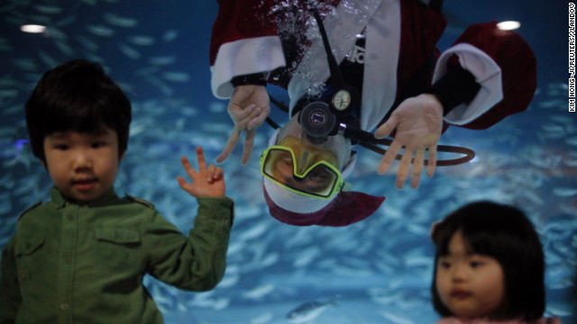 A diver dressed as Santa Claus poses for a photograph with children during a promotional event for the &quot;Sardines Feeding Show with Santa Claus&quot; at the Coex Aquarium in Seoul, South Korea, on December 11.