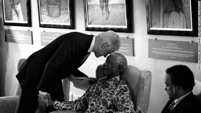 Former U.S. President Bill Clinton leans down to whisper to former South African President Nelson Mandela during a visit to the Nelson Mandela Foundation on July 19, 2007 in Johannesburg.