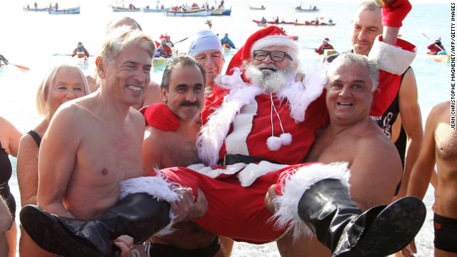 Beachgoers carry a man posing as Santa Claus on the Mediterranean coast on December 8 in Nice, France. 