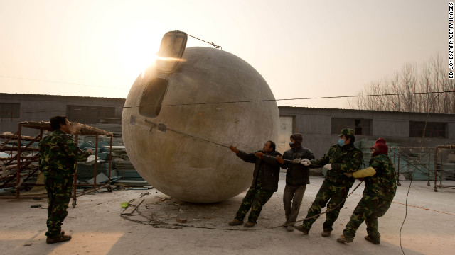 Fours workers team up to re-position one of the survival pods.