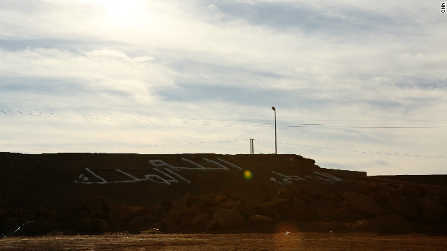 "Letters on a hillside near an entrance to the city of Laayoune read ""God, country, king."""