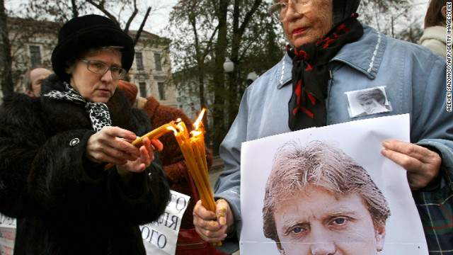 (File photo) Women holding a poster of Alexander Litvinenko light candles in his honor in Moscow on November 22, 2008. 