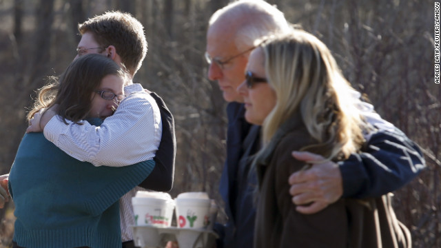 Family members embrace each other outside Sandy Hook Elementary School after Friday's shootings.
