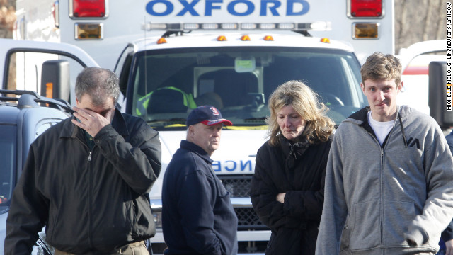 People take in the news outside Sandy Hook Elementary School on December 14.