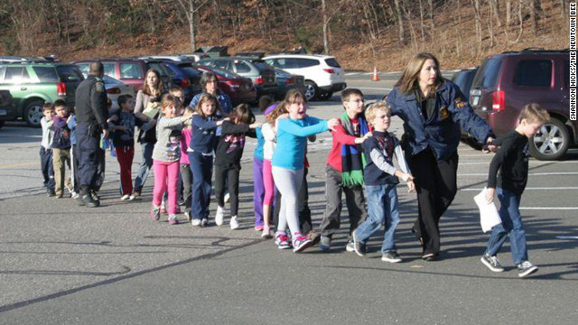 December 14: State police personnel lead children away from Sandy Hook Elementary School in Newtown, Connecticut. A gunman killed 18 children and six adults at the school before he died; two more children died later at a hospital.