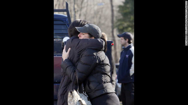 People embrace outside Sandy Hook Elementary School on December 14.