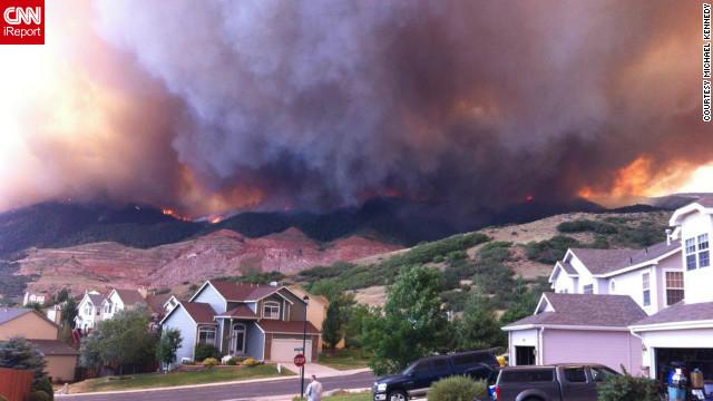 "Wildfires burning in the foothills of the Colorado Springs mountains blanketed a nearby neighborhood with pitch-black smoke in June. ""We ran outside and saw the side of the foothills getting engulfed by flames coming down on either sides of the quarry,"" said photographer Michael Kennedy. ""Our subdivision quickly deteriorated into a war zone with police cars coming into the neighborhood with loud speakers announcing 'leave the area, under mandatory evacuation.'"""