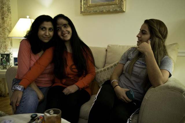 Aesha cuddles up to Jamila Rasouli-Arsala, her mother figure who's away most of the time these days.