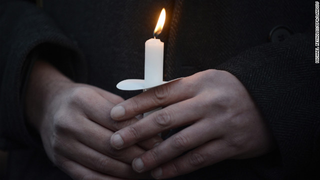 Supporters of gun control hold a candlelight vigil for victims of the shooting outside the White House.