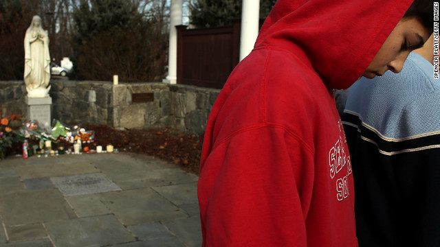 Newtown High School student Trevor Lopez stands outside of a church where residents have come to pray and reflect on Saturday