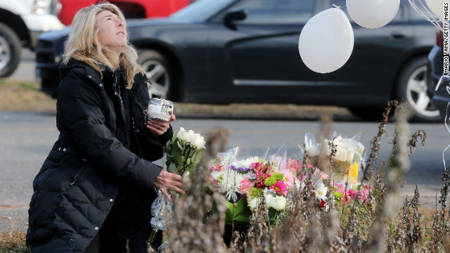 Andrea Jaeger places flowers and a candle at a makeshift memorial outside a firehouse near Sandy Hook Elementary School on Saturday.