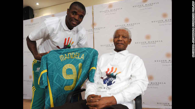 South African defender Aaron Mokoena presents a jersey for the national team to Mandela when meeting before a semifinal match against Brazil, June 2009.