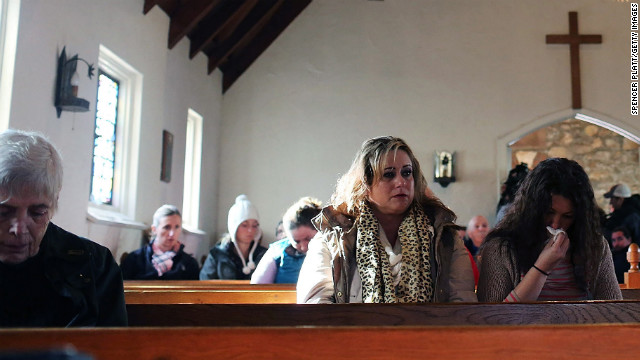 People attend a prayer service in Newtown on Saturday to reflect.