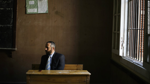 An Egyptian electoral official oversees voting activities as people cast their vote at a polling station in President Mohamed Morsi's hometown Zagazig in the Nile Delta on December 15, 2012.