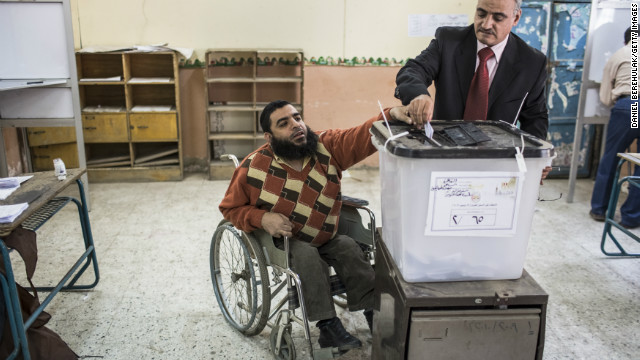 An Egyptian man receives help with dropping his vote in to a ballot box during a referendum on the new Egyptian constitution at a polling station on December 15, 2012 in Cairo, Egypt.
