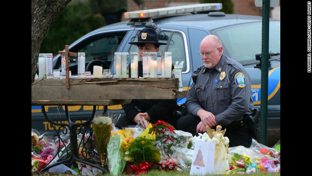 Police officers honor the victims of the school shooting at the St. Rose of Lima Roman Catholic Church on December 16 in Newtown.