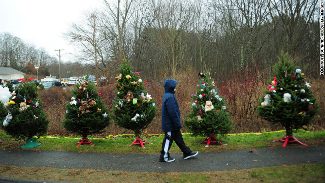 A young boy walks past Christmas trees set up at a makeshift shrine to the shooting victims in Newtown, Connecticut, on December 16.