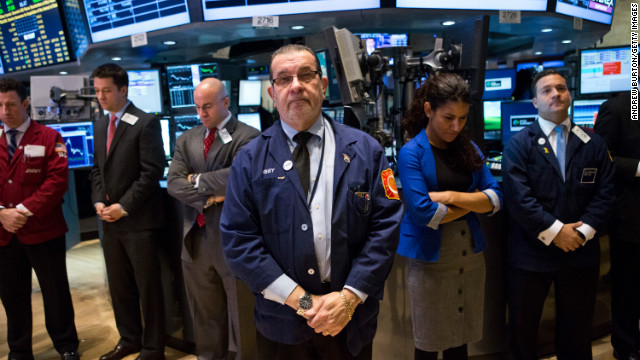 Traders on the floor of the New York Stock Exchange hold a moment of silence on December 17 in honor of the shooting victims.