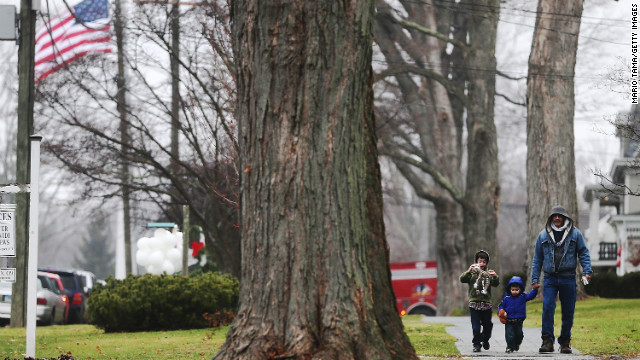Newtown resident Palmer Chiaepetta walks with his sons Jonathan and Jackson as the American flag flies at half-staff in Newtown, Connecticut, on Sunday, December 16, two days after the mass shooting at Sandy Hook Elementary School.