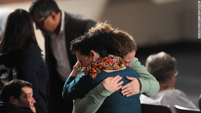 Two women embrace before the interfaith vigil at Newtown High School on Sunday evening. 