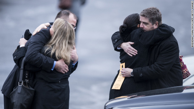 Mourners console each other after the funeral for James Mattioli on December 18.