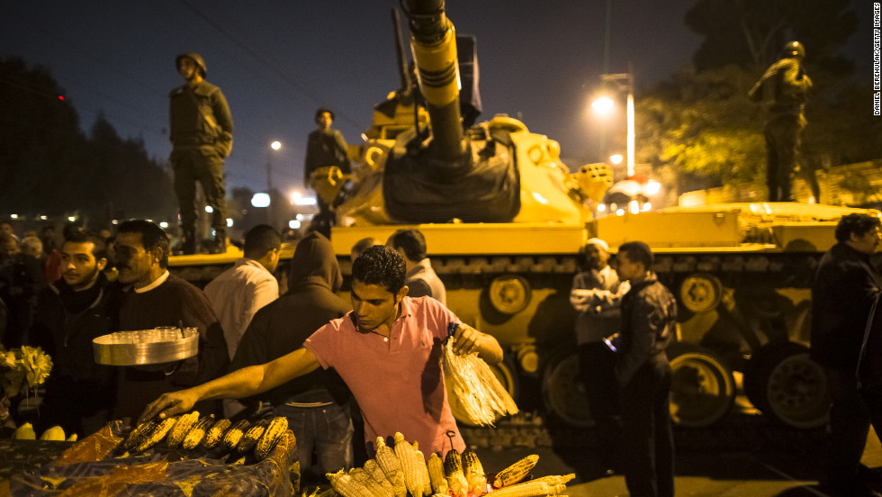 A street vendor grills corn as Egyptian soldiers stand guard at the Presidential Palace on Tuesday, December 18, in Cairo. Protesters opposed to President Mohamed Morsy's first round of voting in the constitutional referendum gather during continuing demonstrations.