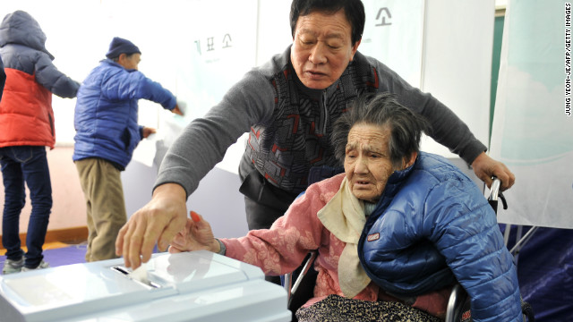 An elderly South Korean woman gets help as she casts her ballot at a polling station in Nonsan, south of Seoul. 
