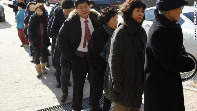 South Korean residents wait in line to cast their votes at a polling station in Seoul.