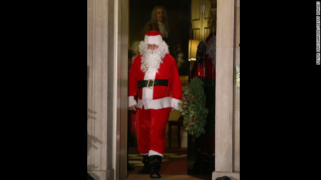 Santa Claus walks out of the front door during a Christmas party hosted for sick children at 10 Downing Street on Monday, December 17, in London.