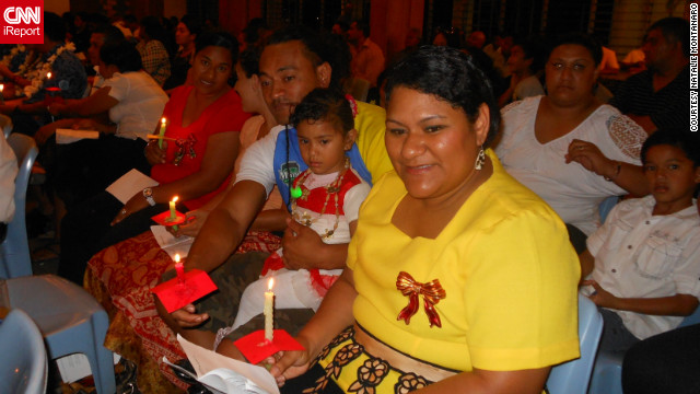 "<a href='http://ireport.cnn.com/people/RomaniaScene'>Natalie Montanaro</a> captured this moment of a happy family attending a carol performance in the Pacific island of Tonga. ""Although we are showered with tropical sunshine, shaded by coconut palms and quenched by the cool blue of the South Pacific, it's already 'beginning to look (and feel!) a lot like Christmas,"" she said."