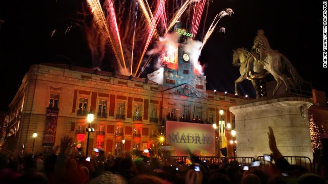Revelers in Madrid's Puerta del Sol eat one grape for each toll of the clock bell at midnight.