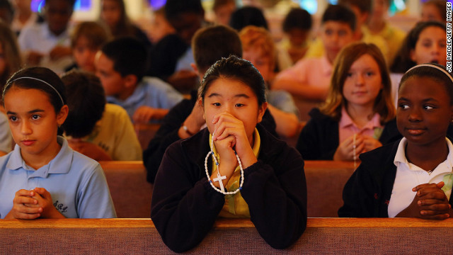 Students participate in a prayer service for victims of the Newtown, Connecticut, mass shooting at St. Rose of Lima School in Miami on Friday, December 21.